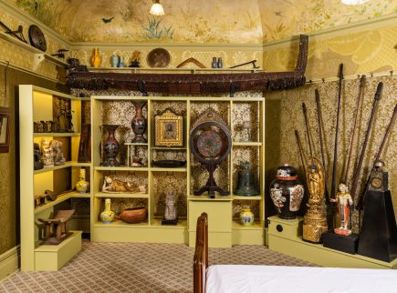 The Russell-Cotes Yellow Room, featuring a display of artefacts and artworks including a Maori Model Canoe