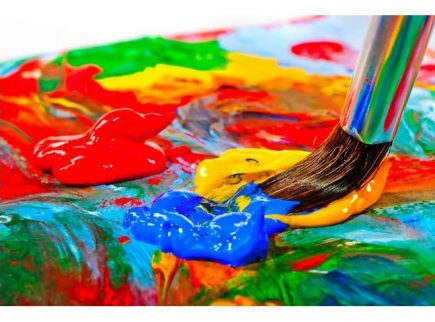 A colourful palette of red, blue and yellow paint and a paintbrush