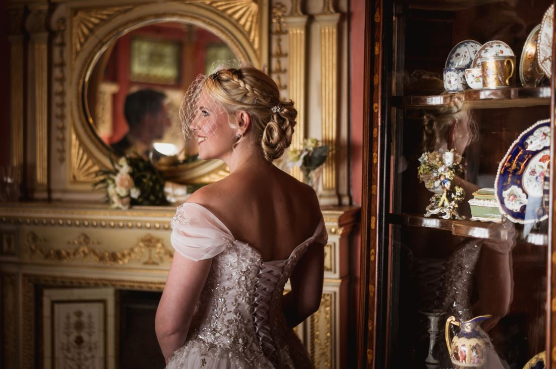 Robin Goodlad Photography. A Bride stands in the Boudoir of the villa, surrounded by lavish decoration and objects. Her groom can just be seen reflected in the mirror. Her blonde hair is intricately tied up, and a light mesh veil falls over her face. She is smiling.