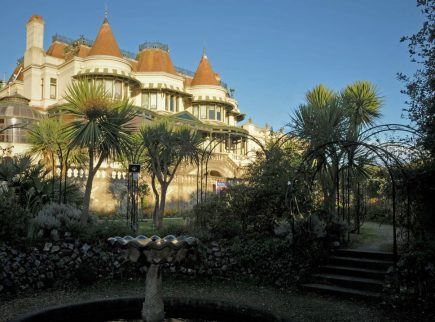 Russell-Cotes villa set against blue sky with garden fountain and trees in the foreground