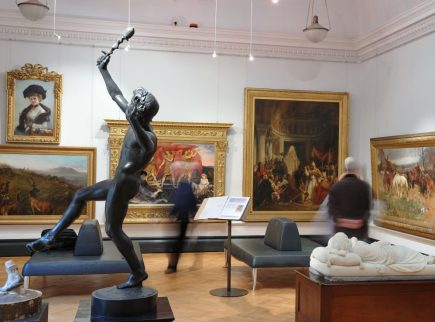 A gallery scene with large gold framed oil paintings on the walls, two people viewing the artworks and sculptures in the foreground